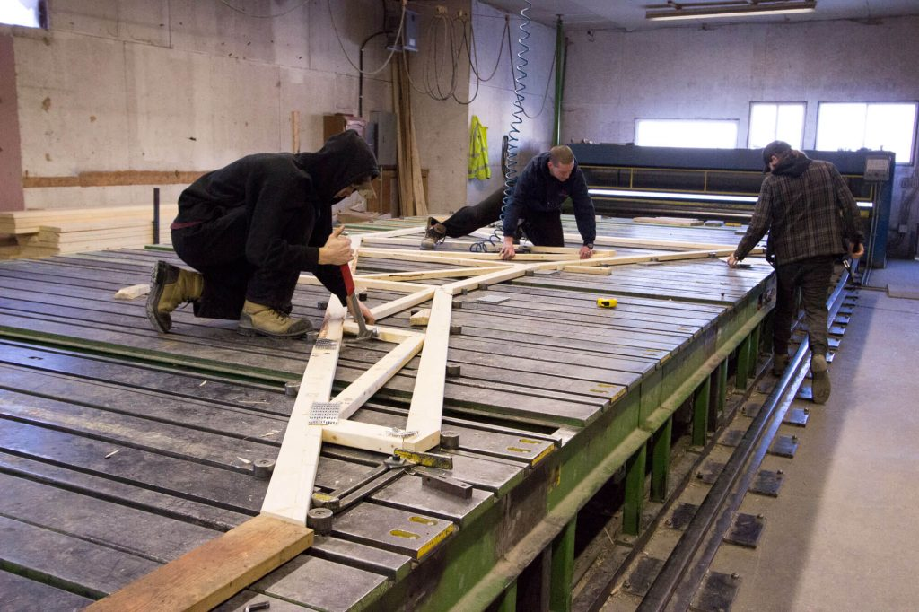 Photo of two men assembling a rood truss